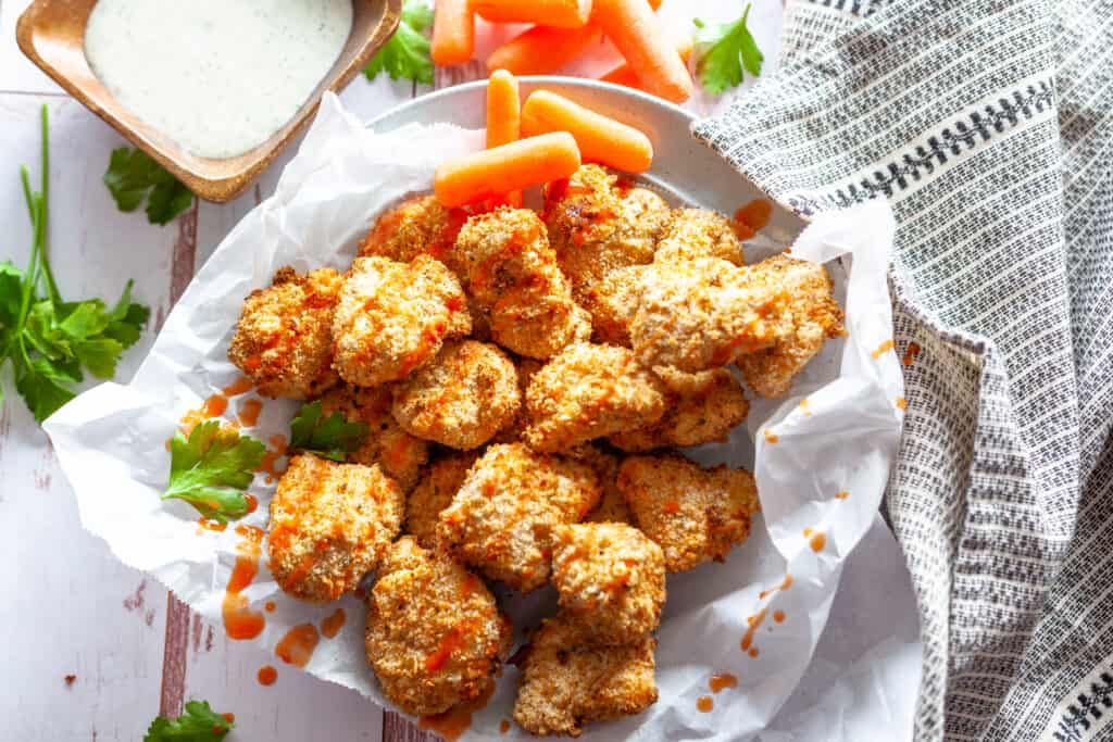Plated buffalo chicken bites with hot sauce