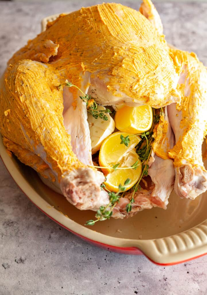 Raw turkey rubbed with flavoured butter, ready for reasting