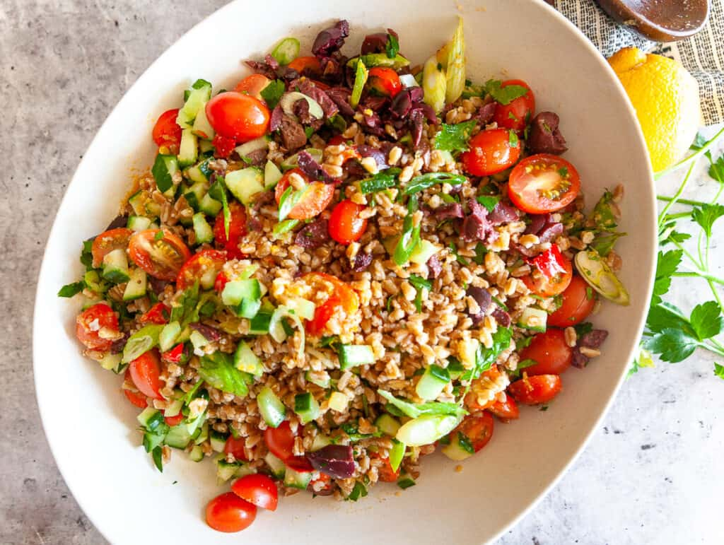 Farro salad in a bowl with vegetables and dressing
