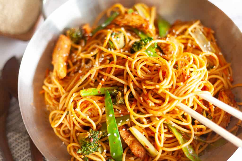 Thai peanut sauce stir fry noodles in a pan with chopsticks