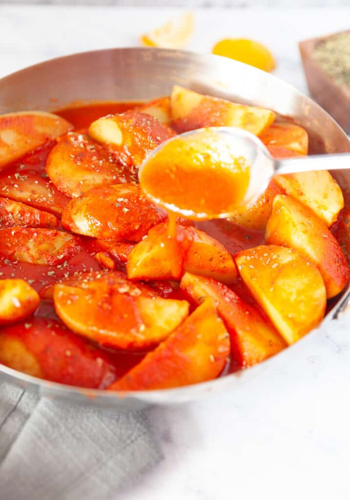 Greek potatoes in a skillet with sauce being spooned over