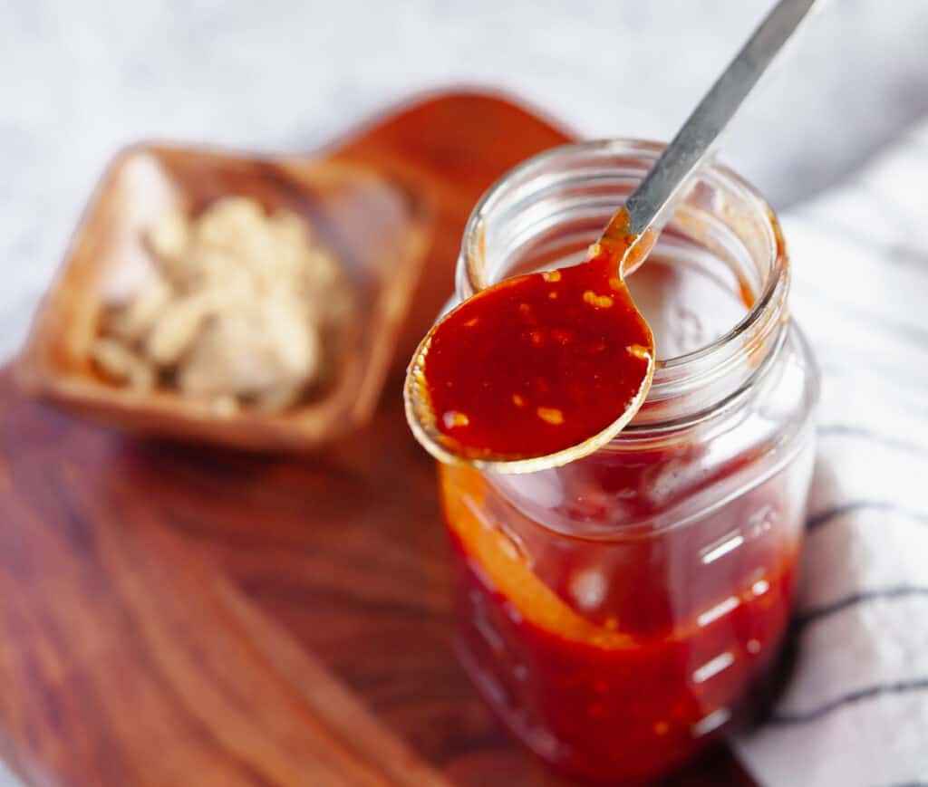 Honey garlic barbecue sauce in a jar with a spoon on top