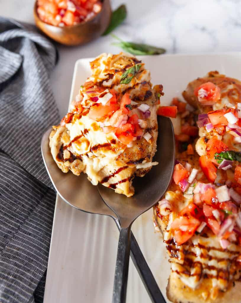 Bruschetta chicken plated with serving spoons