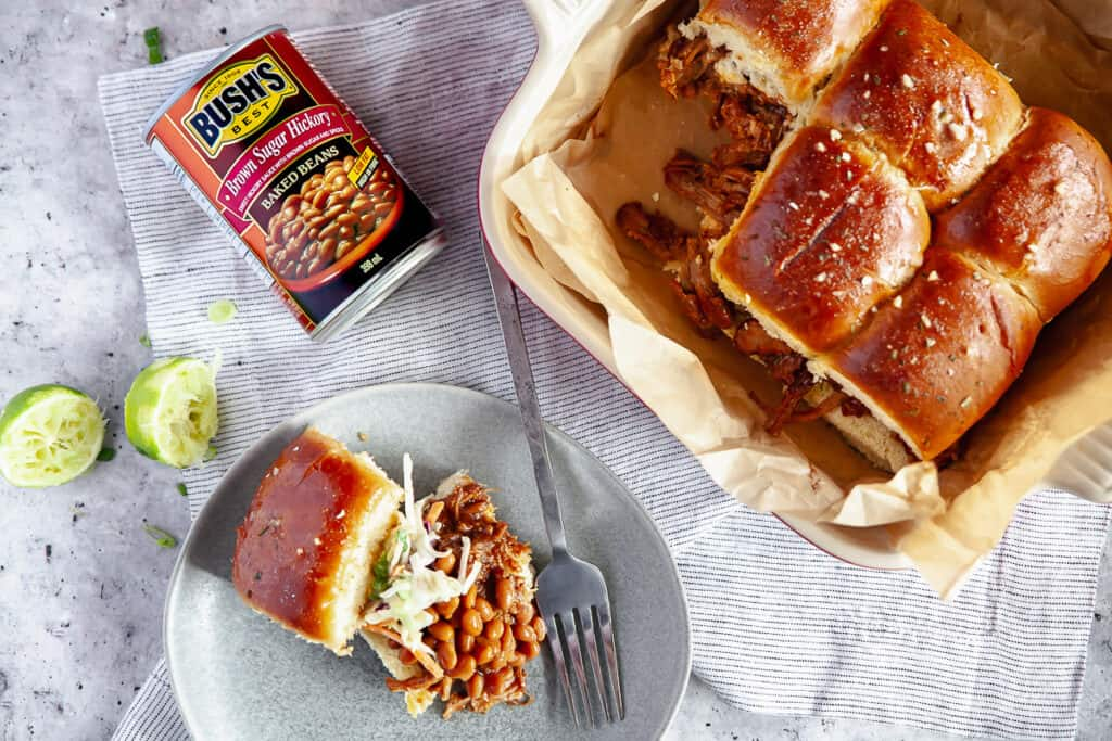 Bush's BBQ pulled pork sliders on a plate, with a baking dish