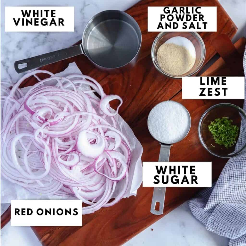 Ingredients for pickled onions laid out on a wooden board, labeled