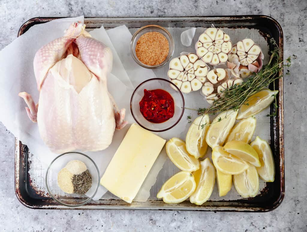 Ingredients for roast chicken laid out on a baking sheet