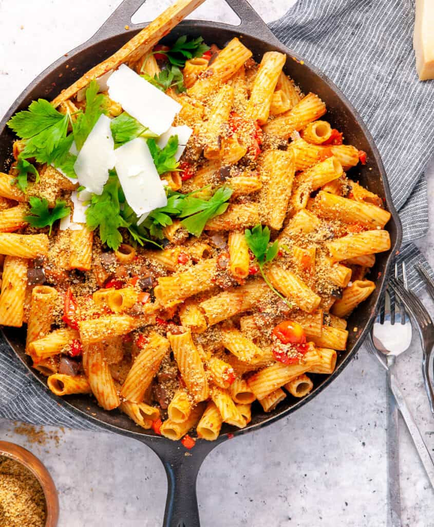 Eggplant and tomato pasta in a cast iron skillet, with forks.