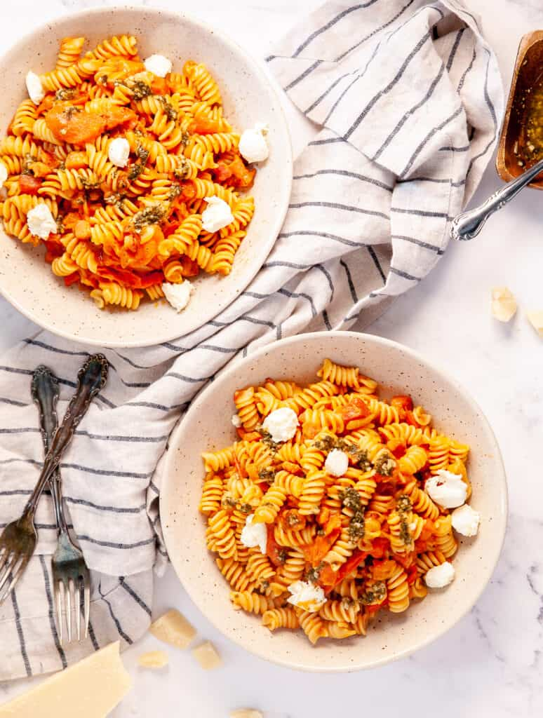 creamy pancetta pasta plated in two bowls, with pesto and bocconcini cheese