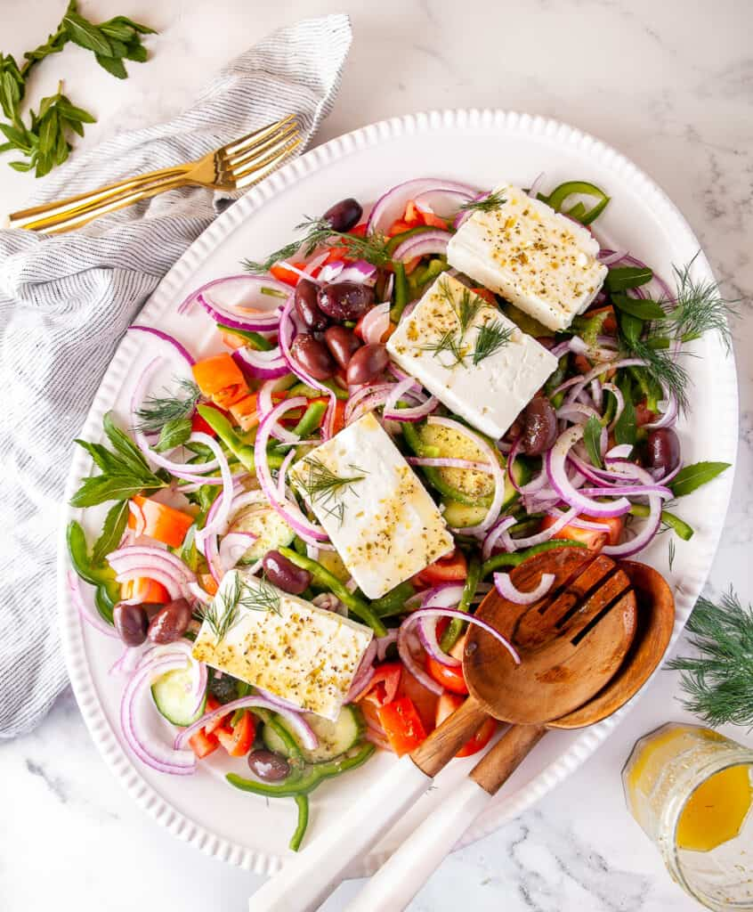 Village greek salad plated on a platter, with mint and dill as a garnish