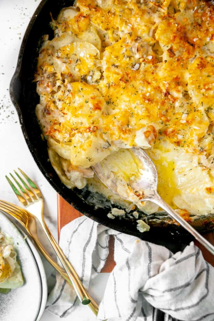 Cast iron skillet potatoes au gratin with a spoonful taken out