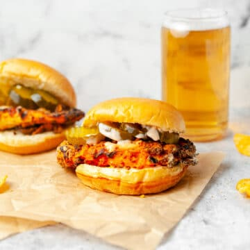 Spicy chicken sandwiches on parchment paper, with a glass of beer